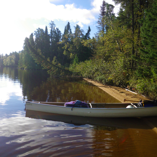 Shoreline of lake with a packed canoe